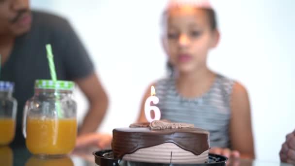 Roztomilá dívka foukání svíčky na narozeninový večírek