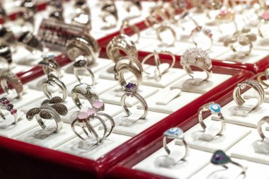 Silver or white gold rings with diamonds and other gemstones jewelry on display jewelry market. Selective focus.