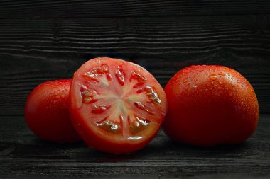tomatoes on dark wooden desk surface