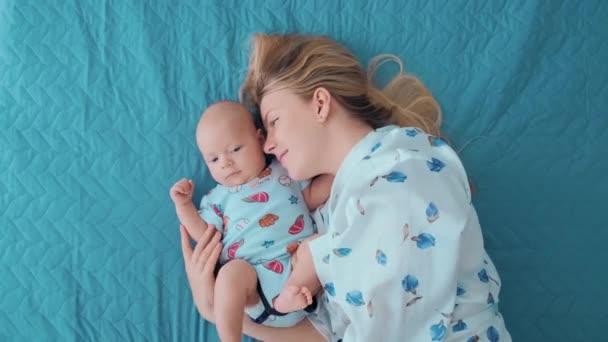 Mladá matka se svým dítětem leží na posteli a baví.