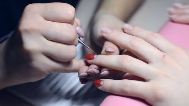 Manikérka maluje nehty s Červený lak v salonu