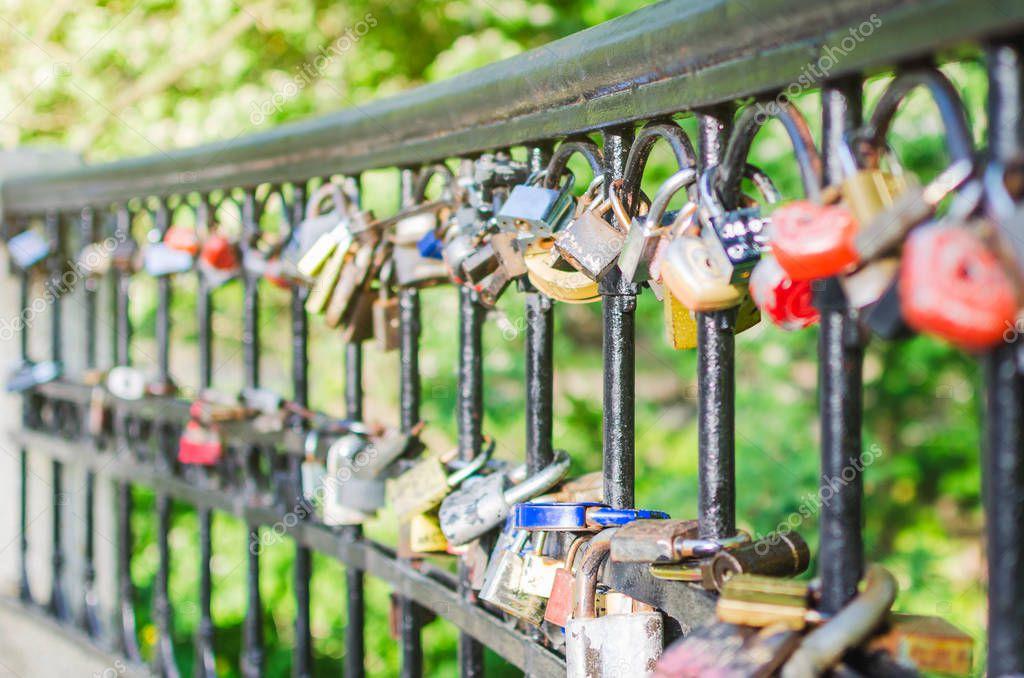 Hinged love locks hanging on a bridge