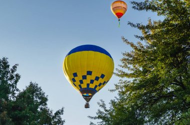 Colorful hot air balloon is flying in the blue sky above the trees