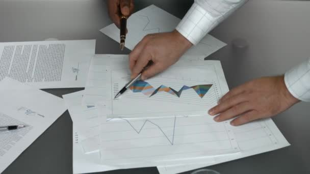 business charts and hands papers with graphs