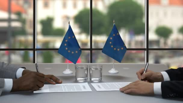 businessmen sign papers handshake near flags of eu