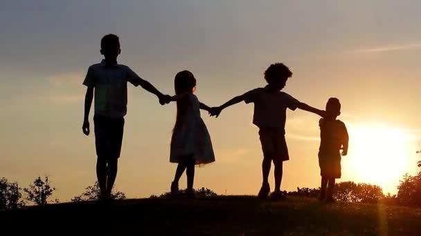 děti jdou spolu na pozadí krásného západu slunce