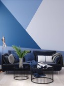Luxury modern blue living room interior with geometric form patterned wall, dark blue sofa, floor lamp and coffee table , 3d render
