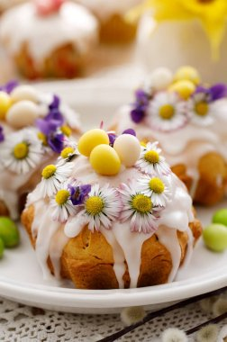 Easter cakes covered with icing decorated with spring and edible flowers on an Easter table. Easter delicious dessert