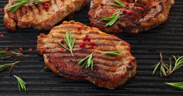 Grilování vepřových steaků, vepřová krkovička s bylinkami a kořením na grilu, pohled shora, 4k. Grilované maso, velký černý, gril
