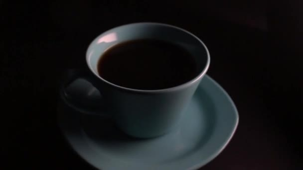 Coffee cup spinning slowly on table.