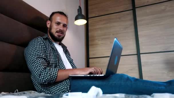 junger Amerikaner mit Kopfhörer liegt auf der Couch und schreibt auf seinem Laptop und telefoniert