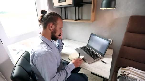 fiatal amerikai srác fülhallgatóval fekszik a kanapén, ír a laptopjára, és telefonon beszél.