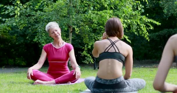 Mistr jógy sedí po tréninku v lotosové pozici a mluví se svými studenty