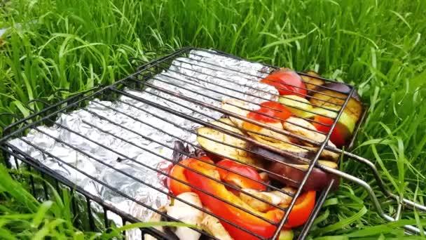 Grillsütő elkészített szeletelt zöldségekkel és fóliába csomagolt haldarabokkal