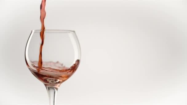 Červené víno vytváří krásnou vlnu. Víno nalévání ve sklenici vína na bílém pozadí