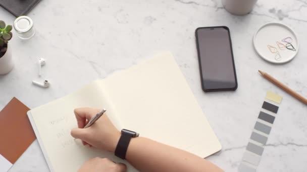 egy tollat használó személy, aki jegyzetfüzetbe ír