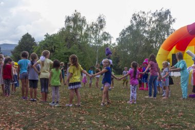Kamennomostsky, Russia - September 1, 2018: Holiday day of the village with animators and children's playgrounds and competitions in the park in the fall