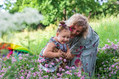 a young mother and her little daughter are having fun happy on a green flower meadow in a Park on a summer day
