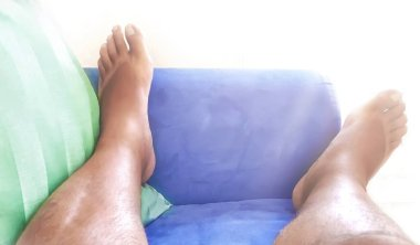 Feet of a bare man resting on a blue sofa with a green pillow. Tiredness and relaxation at home. Rest on the sofa