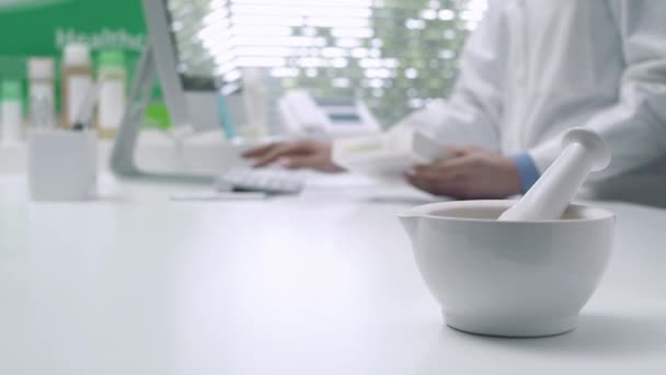 Pharmacist holding a medicine box and searching items on the computer database, mortar and pestle on the foreground: medicine and pharmaceuticals concept