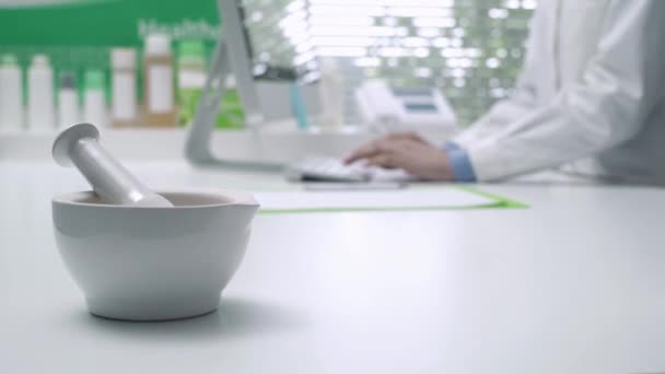Professional pharmacist working with a computer and connecting online, mortar and pestle on the foreground: medicine and technology concept