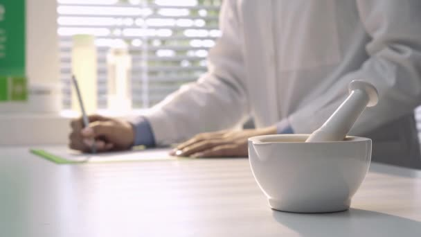 Professional pharmacist working in the laboratory and writing a prescription, mortar and pestle on the foreground, medicine and pharmacy concept
