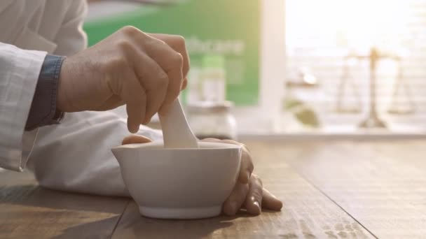 Professional pharmacist and herbalist preparing medicine using a pestle and mortar, herbal medicine and pharmacy concept
