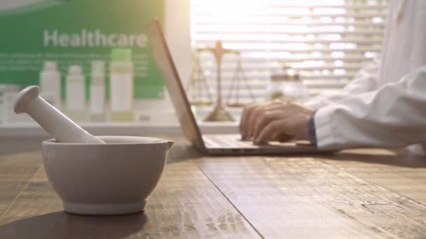 Professional pharmacist working with a laptop and searching for medical preparations online, mortar and pestle on the foreground: pharmacy and herbal medicine concept