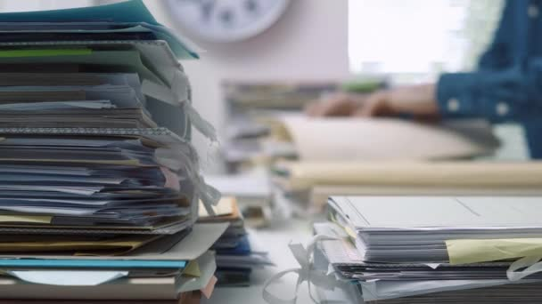Employee working in the office with piles of files and paperwork, business administration and management concept