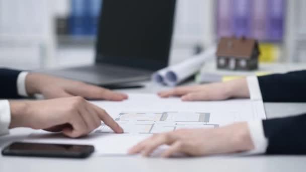 Realitní agent ukazující projekt domu k zákazníkovi
