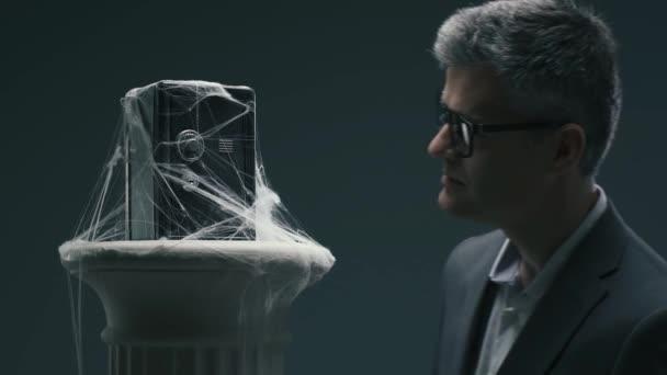 Zamyšlený zklamaný podnikatel při pohledu na bezpečném místě prašné pokryté pavučinami, zmrazené prostředky a neúspěšné dlouhodobé investice koncepce