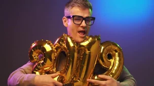 Veselá zábavná pitomce chlapa hospodářství balóny a slaví Nový rok 2019, je tanec a těší