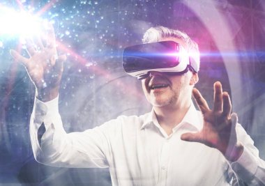 Man experiencing a virtual reality environment, he is wearing a VR headset and interacting with his hands