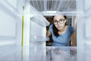 Sad woman looking into her empty fridge with no groceries
