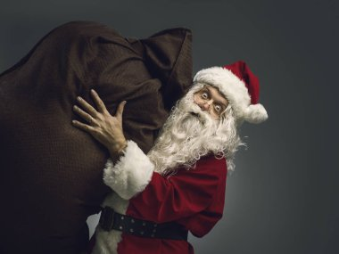 Santa Claus carrying a sack with Christmas gifts