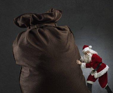 Santa pushing a huge sack with gifts