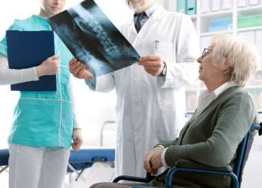 Doctor checking a senior patient's x-ray image