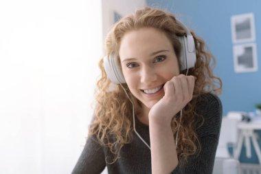 Kulaklıklar ile mutlu gülümseyen kıvırcık kız