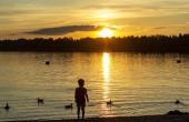 Sonnenuntergang am See in der Sommerhitze an Land Silhouette Kind