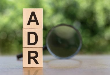 ADR Abbreviation On Wooden Blocks on table with magnifier on green background