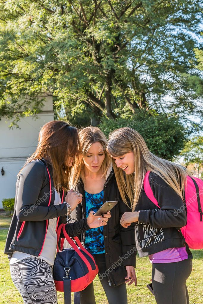 Three young women meet in the park, they greet each other and are happy to meet. They look at the mobile where to go.