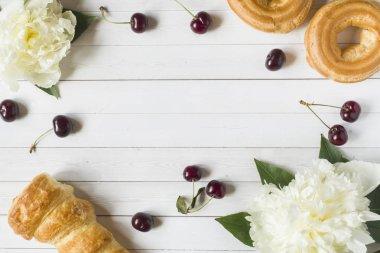 Frame custard cakes cherry peony flowers. Copy space