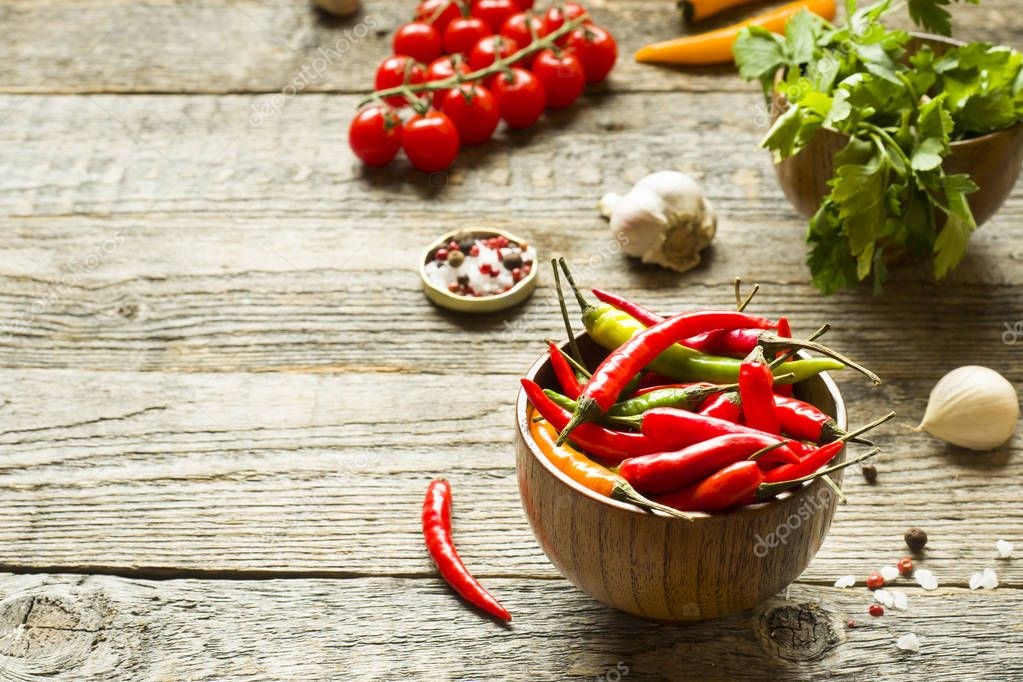 Chili pepper is spicy in a wooden bowl. Tomato parsley garlic on wooden rustic background.
