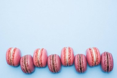Pink dessert macaron or macaroon on blue background top view. Flat lay. Copy space