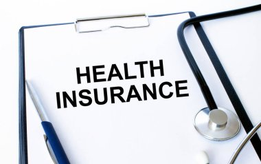 Text Health Insurance on a sheet in the medical folder with a phonendoscope and pen