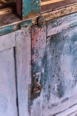 Peeling paint from the front of an old wooden dresser