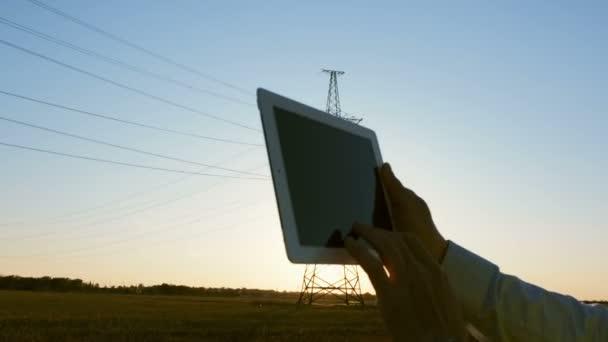 Energetik ve speciálních šatech drží v rukou tablet na pozadí vysokonapěťového sloupu elektrického vedení a zkoumá jeho stav.