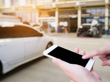Female hand holding mobile smart phone on car service centre or garage blur background