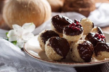 Delicious coconut cookies balls dipped in chocolate and decorated with dried cranberries