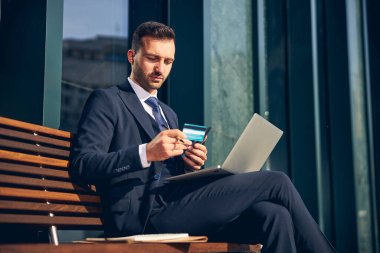 Serious businessman staying alone outside with devices